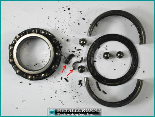 Photograph of a large seized bearing disassembled after cutting the outer race showing the grease had turned to a black thick sludge. Note the fractured cage pieces (arrows) and the liberated balls.