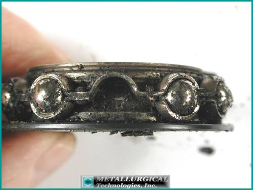 Photograph of the cage, balls and inner race from a large seized bearing showing the thick, black sludge and particulate coating the inside. Note the fractured cage.