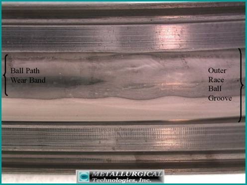 Photograph of a large bearing outer race ID ball path showing wear on one side, indicative of axial (thrust) loading.