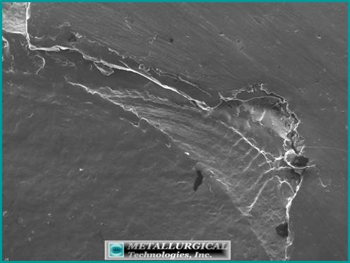SEM image of the edge of one of the small seized bearing ball spalls showing crack progression marks indicative of contact fatigue.