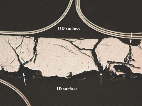 Optical microscopic overview of the longitudinal tube cross-section through the circumferential crack tip exhibits an extensive network of SCC cracks extending from pitted areas. A heavy ID oxide layer is just visible along the ID.