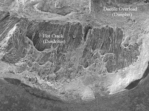 "A SEM photomicrograph of the ductile and hot crack region adjacent to the inner brake boss machined slot. The surface topography is composed of ""dimpled"" (ductile overload) and dendritic (hot crack) structures."