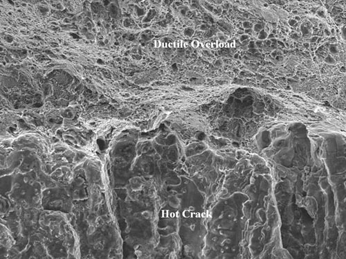 A higher magnification SEM view of the transition from ductile overload to the dendritic hot crack structure presented in Figure 11.