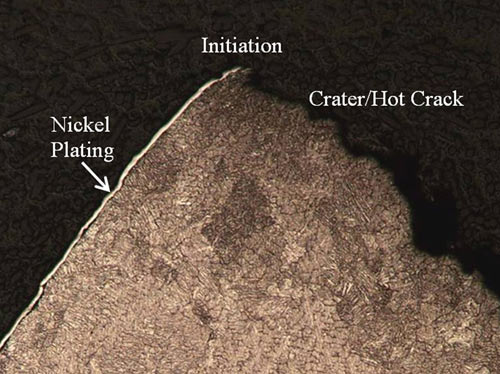 A higher magnification optical photomicrograph of the crater crack initiation site. A thin nickel-plating layer is observed along the weld outer surface.