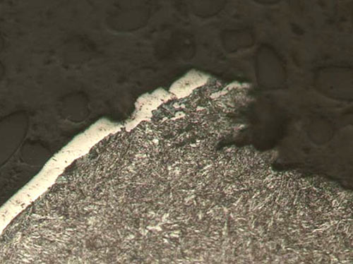 A high magnification optical photomicrograph of the crater crack initiation site. The nickel-plating layer is readily resolved. There is no nickel-plating present along the fracture surface.