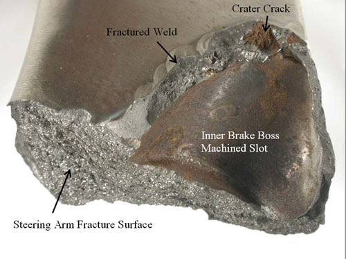 A closer view of the fractured weld joint on the steering arm. A pre-existing crater crack with a rusted/oxidized surface is visible along the upper portion of the weld fracture surface. The pre-crack is located where the welding process stopped.