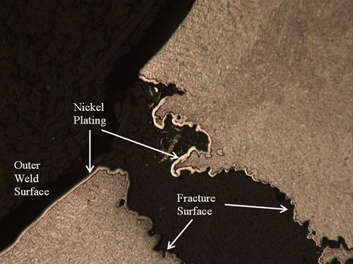 A high magnification optical photomicrograph of the crack opening presented in Figure 27. Nickel plating lines the fracture surface, indicating the crack was present prior to application of the plating.