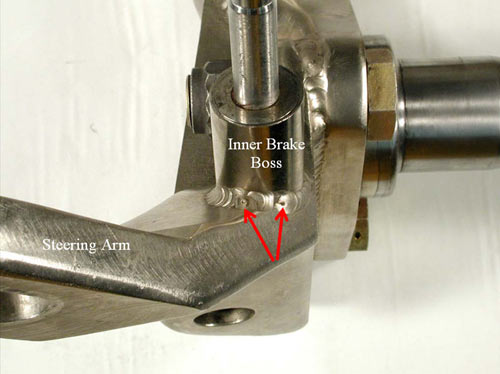 A close-up view of the comparison steering arm and inner brake boss. Another two crater cracks (arrows) are barely visible in the fillet weld joint.